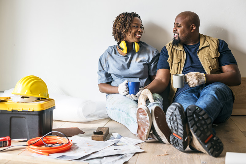 couple sitting rejoicing in home improvements to increase the value of their home.