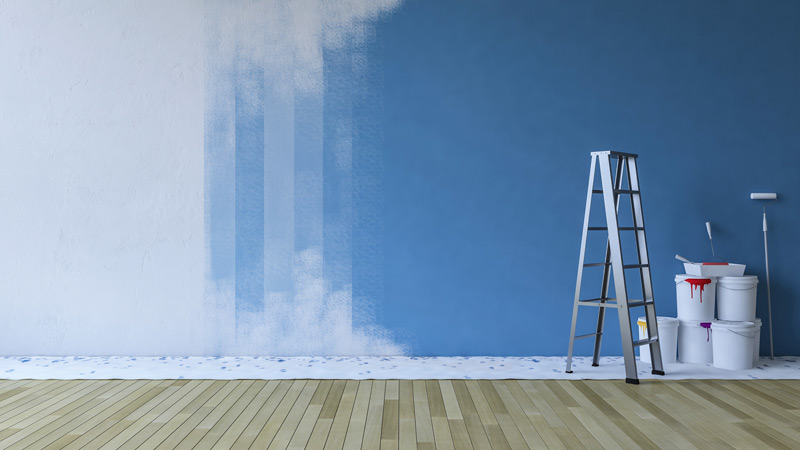 blue wall of home interior paint with ladder and paint buckets