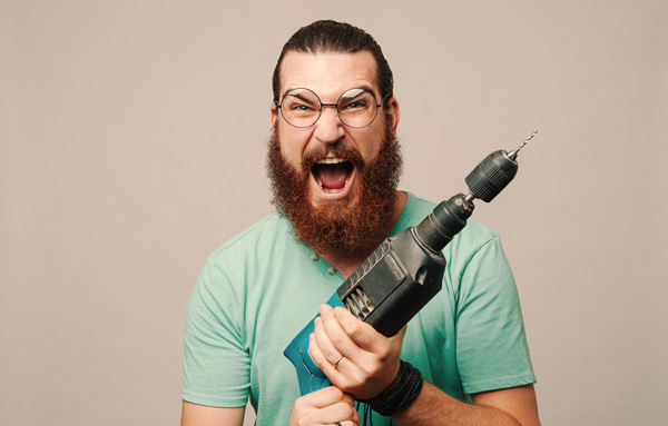 man ferociously holding a power tool - too much? or do we need hand tools? He is very excited about power tools.